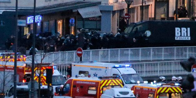 Police officers storm the kosher market where a gunman held several hostages, in Paris, Friday Jan. 9, 2015. The assault came