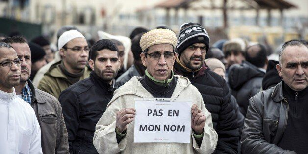 A Muslim man holds a placard, reading 'Not in my name', during a gathering on January 9, 2015 near the mosque of Saint-Etienn