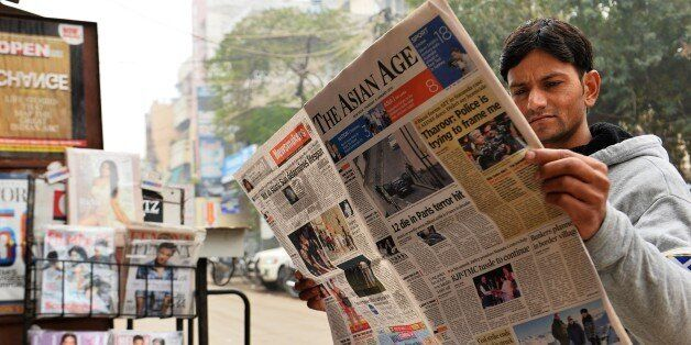 A reader holds up a copy of an English-language Indian newspaper with a front page report on the attack by gunmen on French s
