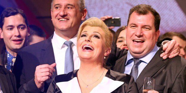 The presidential candidate of the conservative Croatian Democratic Union (HDZ), Kolinda Grabar-Kitarovic (C), celebrates next