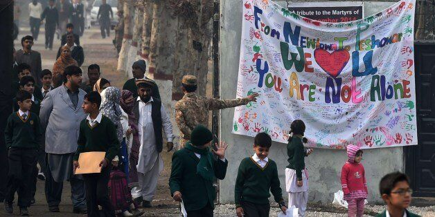 Pakistani parents leave the Army Public School with their children after it was reopened following an attack there by Taliban