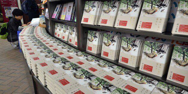 Customers read books by Japanese author Haruki Murakami as Murakami's new novels of the book 'Onna no Inai Otokotachi' which