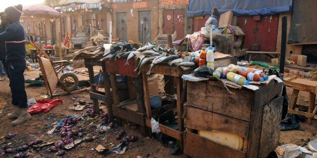 An ecavuated fish stand is seen as Nigerian security inspect the site of a bomb blast at the Jos Terminus Market, on December