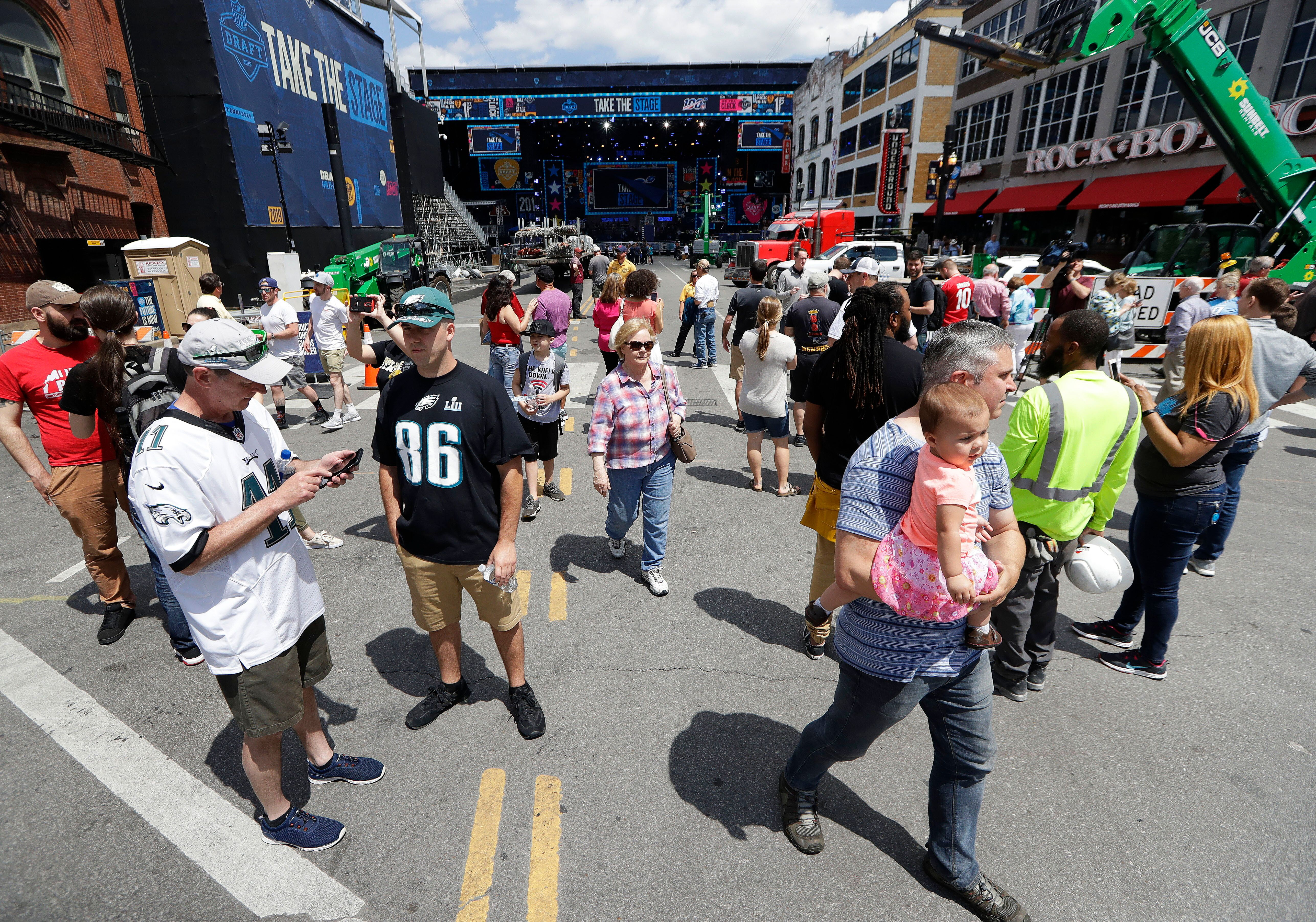 Onlookers watch the progress of the NFL stage being built ahead of the first-round NFL Draft in Nashville, Tenn. (AP Photo)