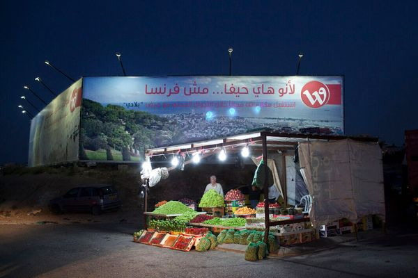 June 2013, Qalandya, Ramallah, West Bank. Behind the fruit vendor, the biggest advertizing sign in the Palestinian territorie