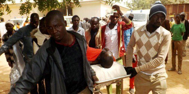 A man injured in a suicide blast is transported at the General Hospital in northeast Nigerian town of Potiskum on January 12,