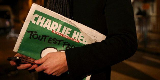 PARIS, FRANCE - JANUARY 13:  A journalist holds an early copy of a Charlie Hebdo magazine while delivering a news report outs