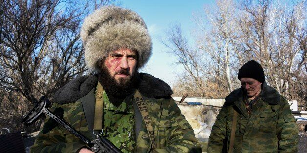 In this Wednesday, Jan. 14, 2015 photo Russian-backed separatist Cossack, stands on guard at the check-point north of Luhansk