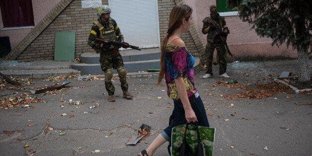 """A woman walks past Ukrainian government soldiers from battalion """"Donbass"""" guarding an entrance of a shop in village Mariinka"""