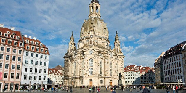 In this picture taken Oct. 16, 2014 people cycle  in front of the 18th century Frauenkirche cathedral (Church of Our Lady) in