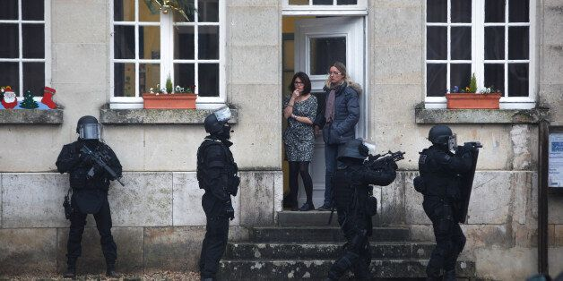 FILE – In this Thursday, Jan. 8, 2015, file photo, French police conduct house to house searches in Longpont, north of Pari