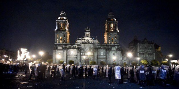 Riot police hold their position outside the National Palace during clashes with protesters over 43 missing students in Mexico
