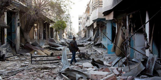 In this Wednesday, Nov. 19, 2014 photo, a Kurdish fighter walks through rubble in Kobani, Syria. In a surprising display of r