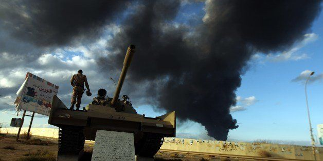 A member of the Libyan army stands on a tank as heavy black smoke rises from the city's port in the background after a fire b