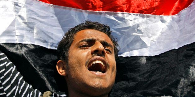 FILE - In this Thursday, Feb. 10, 2011 file photo, a Yemeni demonstrator shouts slogans while raising his national flag durin