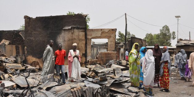 FILE- In this Sunday, May 11, 2014 file photo, people stand outside burnt houses following an attack by Islamic militants in