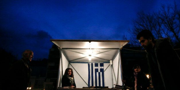 A Greek flag is seen inside a kiosk of the New Democracy party, as people walk by in Athens on Tuesday, Jan. 20, 2015. Weeken