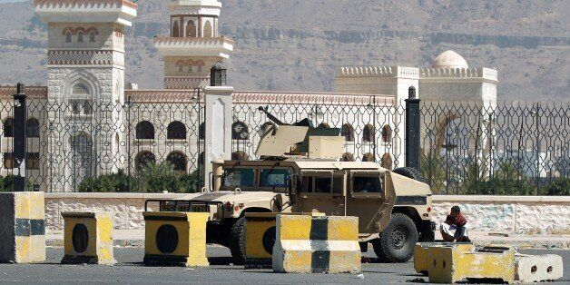 A Shiite Huthi militiaman sits near a tank confiscated from the army in the area around the presidential palace in the capita