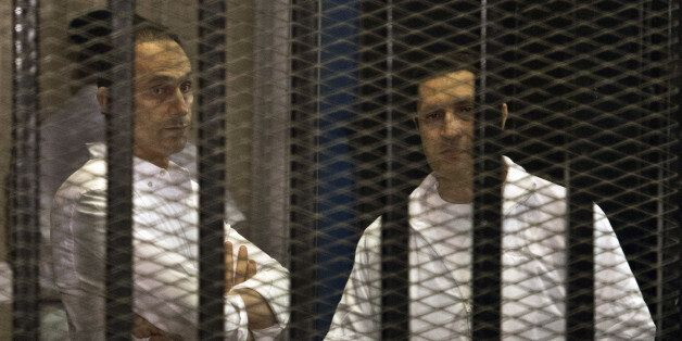 The sons of ousted Egyptian president Hosni Mubarak, Alaa (R) and Gamal are seen behind the defendants' cage during their ret