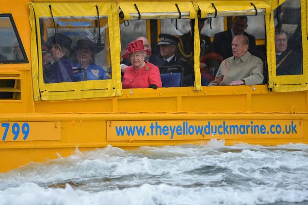Queen Elizabeth II and Prince Philip, Duke of Edinburgh take a ride on the Yellow Duck and amphibious vehicle during a visit