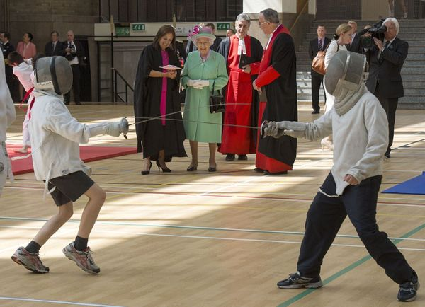 Queen Elizabeth II watches pupils fencing at the sports centre that she officially opened at Westminster School in London on