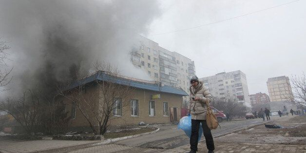 A woman resident passes by a burning house in Mariupol, Ukraine, Saturday, Jan. 24, 2015. A crowded open-air market in Ukrain