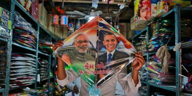 An Indian shopkeeper displays a kite with portraits of India's Prime Minister Narendra Modi and U.S. President Barack Obama a