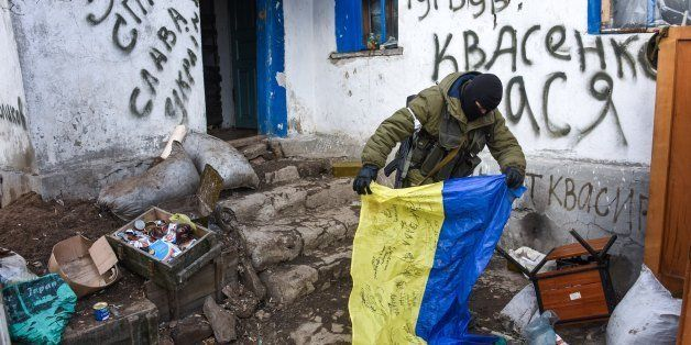 A pro-Russian rebel holds a Ukrainian flag found in a check-point captured by pro-Russian rebels, at the town of Krasniy Part