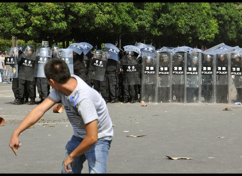 In this photo taken Sunday, Sept. 16, 2012, Chinese police in anti-riot gear use their shields to block projectiles thrown at