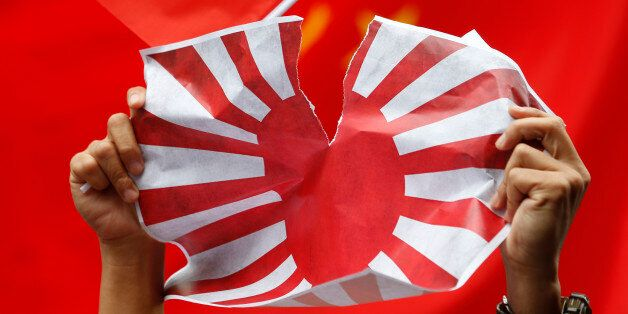 FILE - In this Aug. 16, 2012 file photo, an anti-Japan protester tears Japanese Rising Sun Flag during a rally outside the Ja