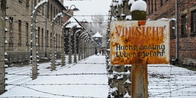 Visitors walk between barbed wire fences at the Auschwitz Nazi death camp in Oswiecim, Poland, Monday, Jan. 26, 2015. A decad