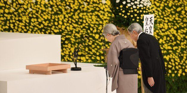 Japanese Emperor Akihito (R) and Empress Michiko (L) bow before the altar during an annual memorial service for war victims i