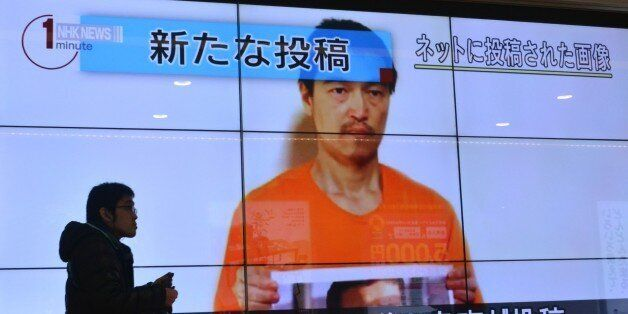 A pedestrian looks at a large screen in Tokyo on January 28, 2015 showing television news reports about Japanese hostage Kenj
