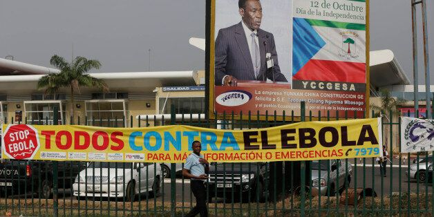A man walk past sign saying we are all against Ebola at the Malabo International Airport in Malabo, Equatorial Guinea, Saturd