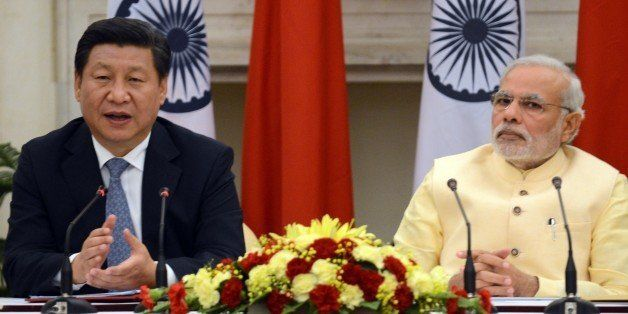 Chinese President Xi Jinping (L) speaks as Indian Prime Minister Narendra Modi looks on as they issue a joint statement in Ne
