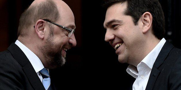 Greek Prime Minister Alexis Tsipras (R) smiles as he welcomes European Parliament Chairman Martin Schulz before their meeting