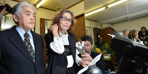 Junko Ishido (C) mother of Kenji Goto, speaks to reporters while her husband Yukio Ishido (L) stands beside her at their home