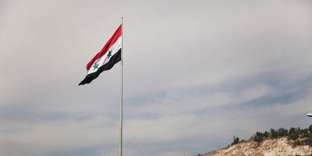 In this Monday, Oct. 27, 2014 photo, a Syrian flag flies over the capital, Damascus, Syria. Syrians are adjusting to life in