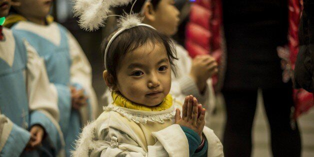 A young Chinese worshipper attends the Christmas Eve mass at a Catholic church in Beijing on December 24, 2014 as Christians