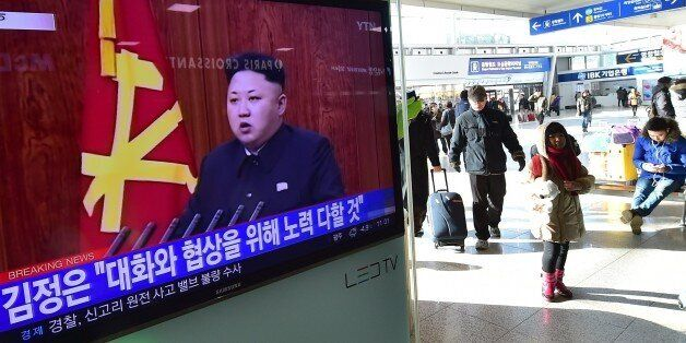 Travellers walk past a television screen showing North Korean leader Kim Jong-Un's New Year speech, at a railroad station in