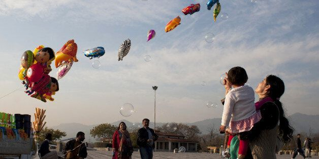 A Pakistani woman shows her daughter bubbles released by a vendor in Lake View park in Islamabad, Pakistan, Saturday, Jan. 24