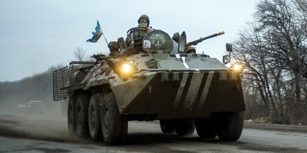 Ukrainian servicemen ride an Armoured Personnel Vehicle (APC) near Artemivsk on February 5, 2015. German Chancellor Angela Me