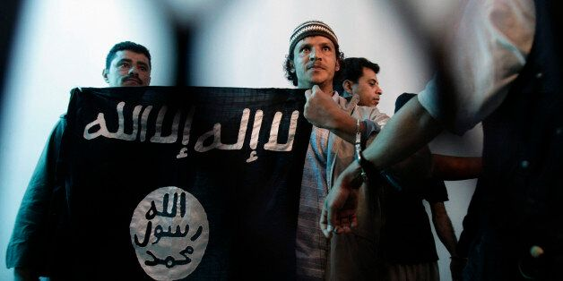 FILE - In this Tuesday, April 23, 2013 file photo, a suspected Yemeni al-Qaida militant, center, holds an Islamist banner as