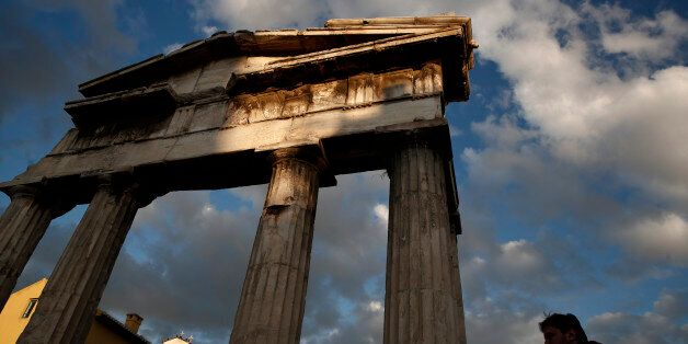 A man walks in front of the Gate of the ancient Roman agora, in central Athens, Saturday, Feb. 7, 2015. Greek Premier Alexis