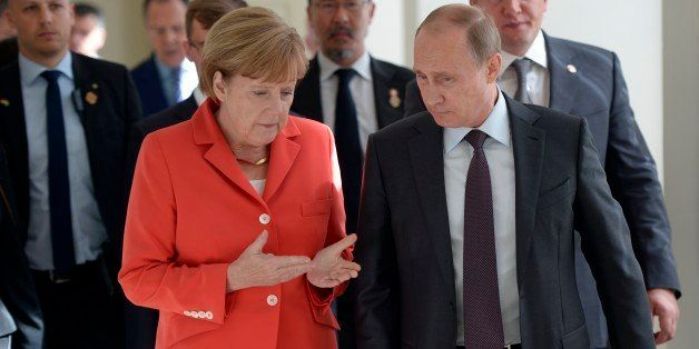 In this photo taken on Sunday, July  13, 2014 Russian President Vladimir Putin, right, and German Chancellor Angela Merkel sp