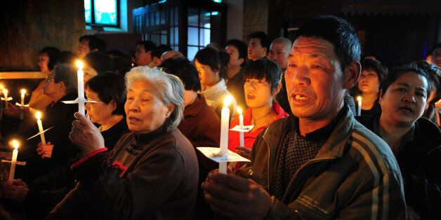 Chinese Catholic pray as they attend an Easter service at the historic South Cathedral in Beijing on April 7, 2012.  Easter c