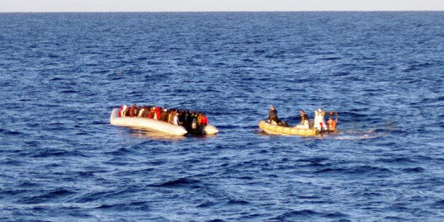 In this photo taken on Thursday, Dec. 4, 2014 provided by the Italian Navy, a rescue crew on a dinghy, right, approaches migr