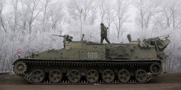 Ukrainian government soldier walks atop of his armored vehicle on the road between the towns of Dabeltseve and Artemivsk, Ukr