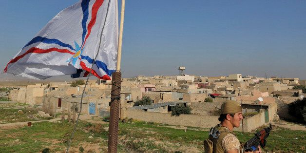 A Dwekh Nawsha militia member stands next to a flag of the Assyrian Patriotic Party, as he stands guard on the rooftop of a b