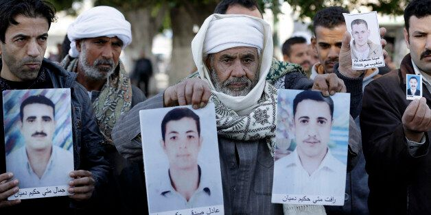 Coptic Christian men whose relatives were abducted in Libya hold their photos in front of the foreign ministry in Cairo, Egyp